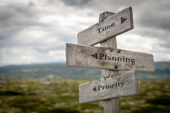 time, planning and priority on wooden road sign outdoors in nature.