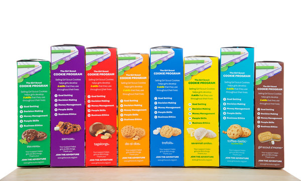 Alameda, CA - February 14, 2018: Brownie Baker brand Girl Scout cookies, all eight flavors on a wood table isolated on white background. Cookie sales raise funds for troop lead events and activities.