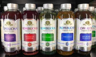 Alameda, CA - March 10, 2018: store shelf with bottles of Kombucha organic and raw probiotic beverage in various flavors. produced by fermenting tea using a symbiotic culture of bacteria and yeast.