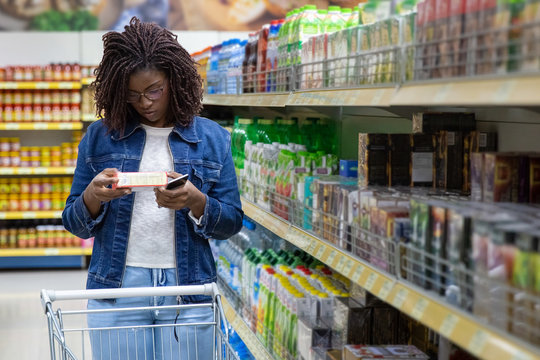 Focused African American woman shopping at grocery store. Serious young customer standing with shopping cart and reading information on packaging. Shopping concept