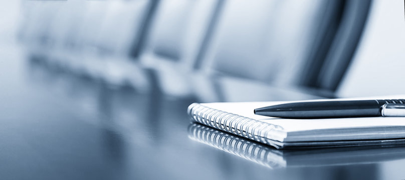Notepad on a table with pen before meeting, blue tone, business concept with copy space