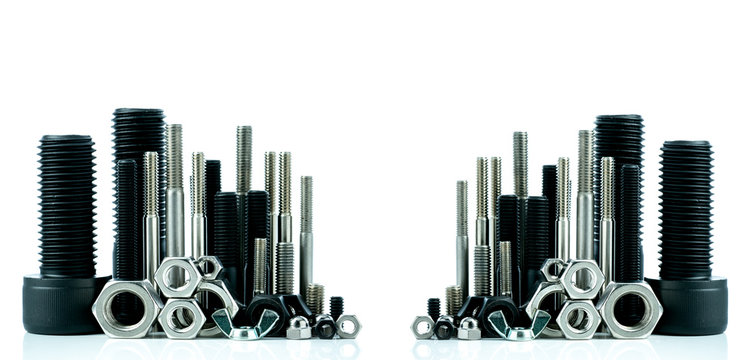Metal bolts and nuts on white background. Fasteners equipment. Hardware tools. Stud bolt, hex nuts, and hex head bolts in workshop. Threaded fastener use in automotive engineering. Hexagonal bolt.