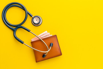 Doctor stethoscope and the new leather brown men wallet on yellow background. Budget for health check or money and financial concept