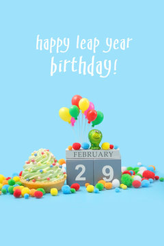 Happy leap year birthday greeting card. February 29 date calendar, Frog, Birthday cupcake, balloons on blue background. leap day in leap year concept.