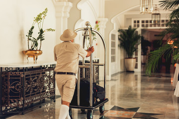 Back view of bellhop pushing luggage cart delivering bags to hotel rooms.