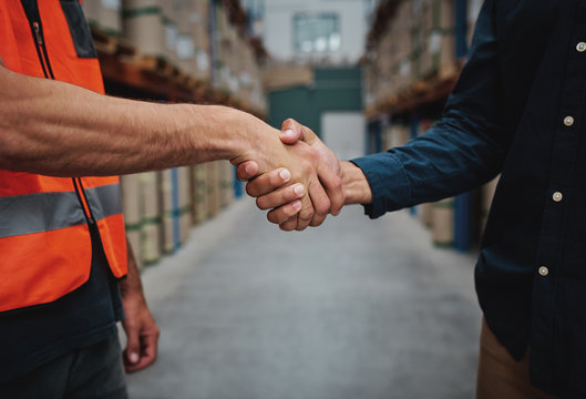 Close-up of two men handshake while concluding agreement about container rent and shaking hands