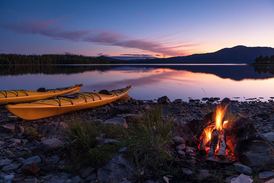 Campfire during dusk at the shore of a lake with two kayaks. Sweden.
