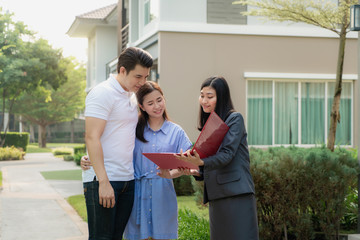 Asian woman Real estate broker agent showing a house detail in her file to the young Asian couple lover looking and interest to buy it. Buying a new house..
