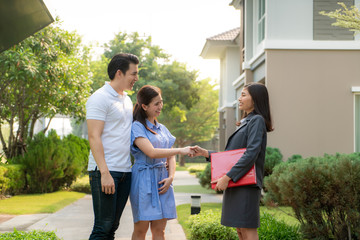 Happy Asian couple looking for their new house and shake hands with real estate broker after a deal. Young couple handshaking real estate agent after signing contract for buy house..