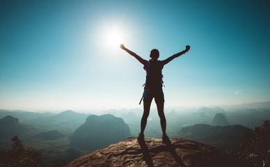 Cheering woman backpacker enjoy the view on sunrise mountain top cliff edge Fotobehang