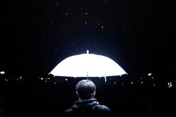 Rear View Of Man Holding White Umbrella At Night