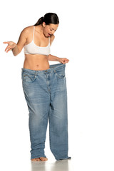 Young slim woman in big size pants on white