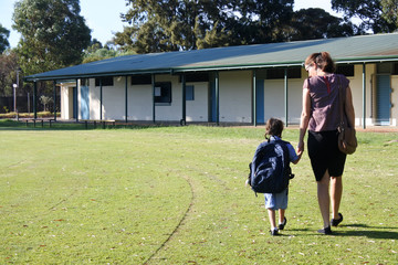 Rear view of mother and daughter walking together to school