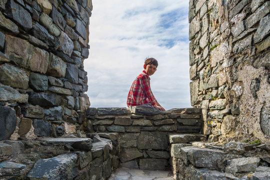 Small boy in castle sitting in old window