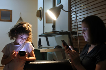 Young girl and mother reading messages on cellphone in home at night