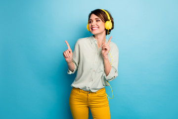 Photo of funny cheerful lady listening radio cool stylish earphones raise fingers discotheque dj dancing wear casual green shirt yellow trousers isolated blue color background Fotobehang