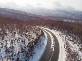 Highway Road cutting through the mountain region between Otaru and Niseko in Hokkaido , Japan