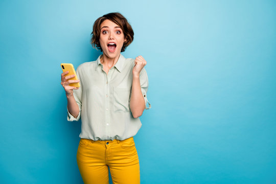 Photo of pretty lady hold telephone open mouth buy smart phone low sale shopping price wear casual green shirt yellow pants isolated blue color background
