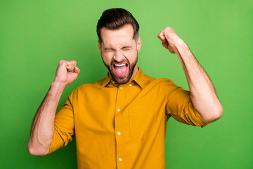 Close-up portrait of his he nice attractive cheerful cheery ecstatic guy in formal shirt celebrating great luck triumph isolated on bright vivid shine vibrant green color background Wall mural