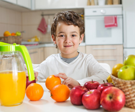 Boy sitting on a table full with fruit