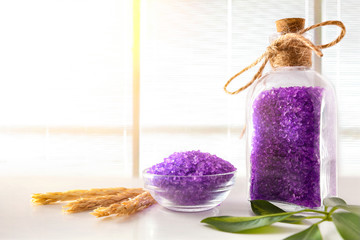 Lilac bath salts on white table and venetian window background