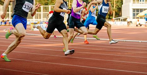 Fototapeta race group man runners sprinters run on track in athletics obraz