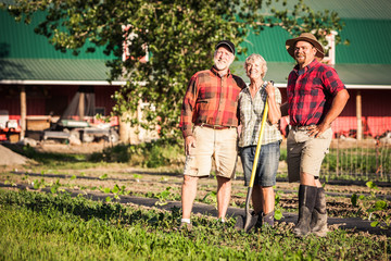 Farming family standing next to rows of vegetables with red barn in background. Laurel, Montana, USA