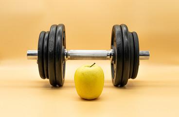 Mancuerna y manzana en fondo de color crema