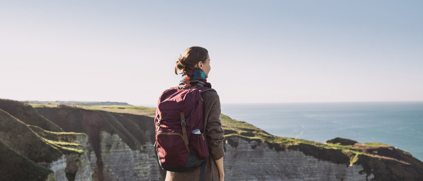 Young tourist woman with backpack looking at sea in Normandy, France over beautiful cliffs background. Travel, active lifestyle and winter holiday concept