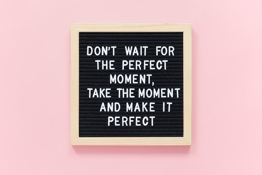 Don't wait for the perfect moment, take the moment and make it perfect. Motivational quote on black letter board frame on pink background. Concept inspirational quote of the day.