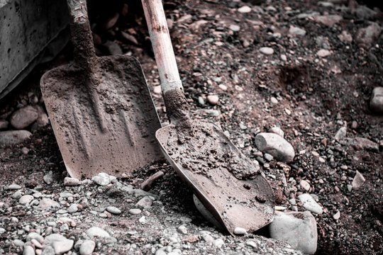 Dirty shovels on construction site. Old shovels with concrete and stones background.