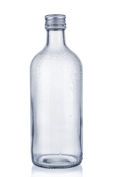 Empty glass bottle with water drops on white background