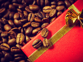 Red gift box on roasted coffee beans.