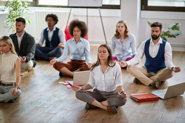 group of business coworkers meditating at work, sitting on the floor. modern, business, meditation concept