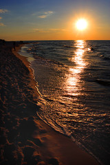 Colorful sunset over beach and seashore waterline of Baltic Sea with peaceful waves in Karwia resort, north Poland, in summer season