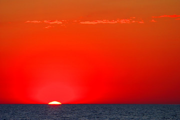 Stores à enrouleur Rouge Colorful sunset over the waterline horizon of Baltic Sea with peaceful waves seen from the seaside beach in Karwia resort, north Poland, in summer season