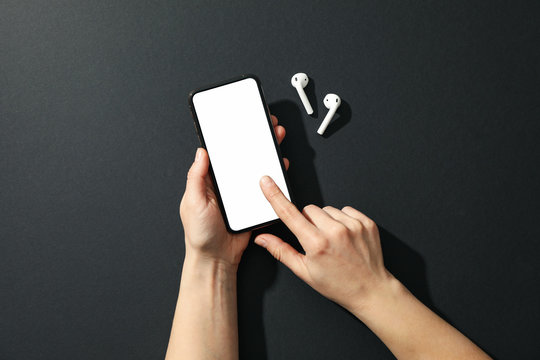 Female holding phone with empty screen and headphones on black background, top view
