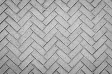 a herringbone pattern brick wall in a neutral gray color