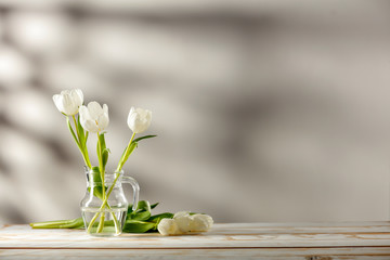 Wall Mural - Desk of free space and fresh spring flowers.Wall with shadows and copy space for your decoration.