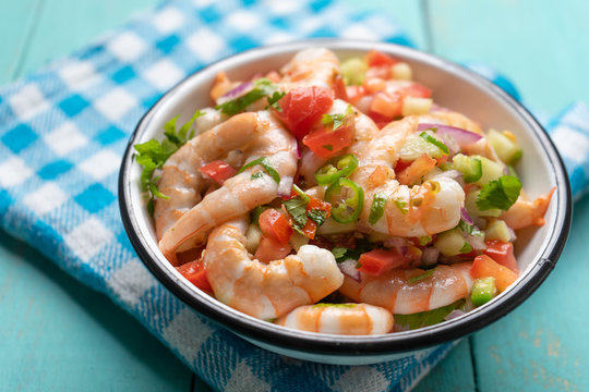 Mexican shrimp ceviche with tomato and serrano pepper on turquoise background