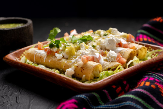 Mexican potato and cheese fried tacos also called flautas with green sauce on dark background