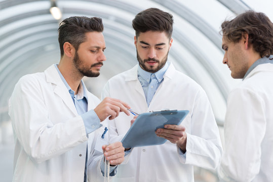 three men in labcoats looking at clipboard