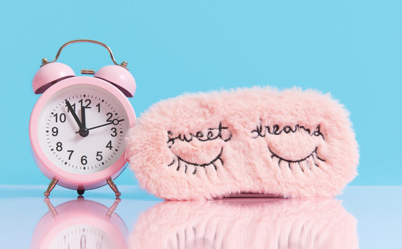 Sleep optimization. Pink fluffy mask for sleeping and a pink alarm clock on a light blue background.