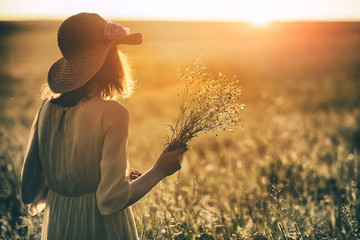 Stylish woman with hat holding grass herb bouquet in summer field enjoying morning sunrise or evening sunset