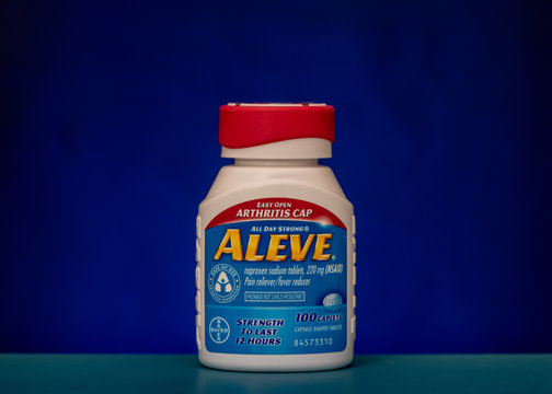 Bottle of Aleve against blue background, side view