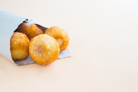 French doughnuts Beignet covered with sugar powder on a brown background