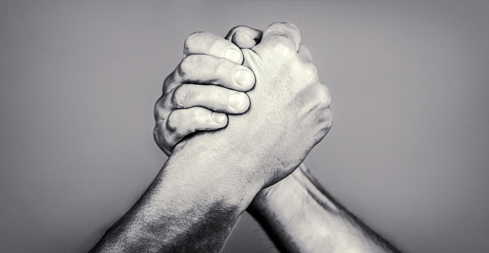 Two men arm wrestling. Arms wrestling. Friendly handshake, friends greeting. Handshake, arms, friendship. Hand, rivalry, vs, challenge, strength comparison. Closep up. Black and whit