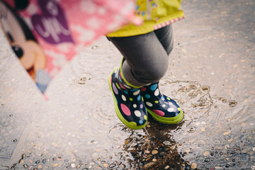 Colorful spotted rain boots baby girl playing with water puddles on a urban scene Wall mural
