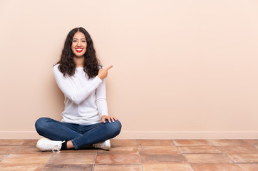 Young woman sitting on the floor pointing back