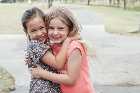 Happy and healthy mixed race multiethnic young little girls hugging and smiling in the park, best friend kids and children friendship, all lives matter, no to racism, equality concept